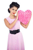 Cute black hair model holding a pink heart shaped pillow — Stock Photo