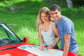 Cheerful young couple reading map on their cabriolet bonnet — Stock Photo