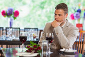 Handsome man waiting for his girlfriend at restaurant — Stock Photo