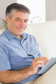 Smiling man sitting on a sofa using a tablet pc — Stock Photo