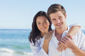 Cheerful couple embracing on the beach — Stock Photo