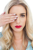 Blonde model in blue dress looking at camera with one eye and hidding the other with her hand — Stock Photo