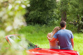 Loving couple admiring nature while leaning on their cabriolet — Stock Photo
