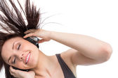 Smiling pretty brunette tossing her hair while listening to music — Stock Photo