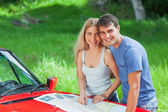 Happy young couple reading map on their cabriolet bonnet — Stock Photo