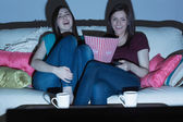 Two laughing friends on the couch watching tv together in the dark — Stock Photo