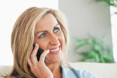Smiling woman calling someone with her mobile phone — Stock Photo