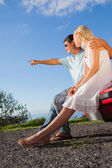 Cheerful cute couple sitting on their cabriolet car hood — Stock Photo