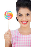 Pleased black hair model holding a colored lollipop — Stock Photo