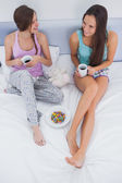 Friends sitting with coffee in bed — Stock Photo