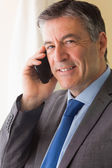 Smiling man calling someone with his mobile phone — Stock Photo
