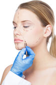 Surgeon drawing dotted lines on beautiful patient — Stock Photo