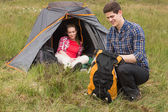 Happy man packing backpack while girlfriend sits in tent — Stock Photo