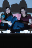 Two smiling friends on the couch watching tv together in the dark — Stock Photo