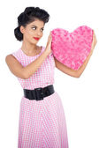 Stylish black hair model holding a pink heart shaped pillow — Stock Photo