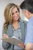 Estate agent showing lease to customer and smiling — Stock Photo