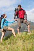 Guapo excursionista ayudando a su novia cuesta arriba — Foto de Stock