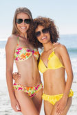 Two pretty friends in bikinis wearing sunglasses posing — Stock Photo