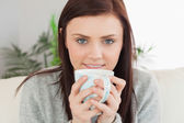 Smiling girl drinking a cup of coffee — Stock Photo