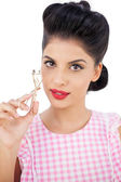Attractive black hair model holding an eyelash curler — Stock Photo