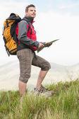 Excursionista guapo con mochila caminando cuesta arriba con un mapa — Foto de Stock
