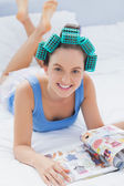 Girl in hair rollers lying in bed — Stock Photo