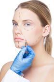Surgeon drawing dotted lines on gorgeous patient — Stock Photo
