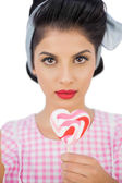 Serious black hair model holding a heart shaped lollipop — Stock Photo