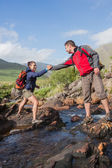 Man helping his pretty girlfriend to cross a river — Stock Photo
