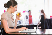 Attractive businesswoman holding wine glass while working on laptop — Stock Photo