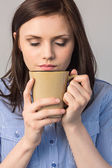 Relaxed pretty brunette smelling coffee — Stock Photo