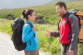 Hikers with backpacks chatting together — Stok fotoğraf
