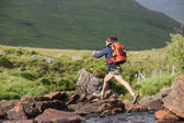 Athletic hiker leaping across rocks in a river — Stock Photo