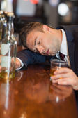 Drunk businessman holding whiskey glass lying on a counter — Stock Photo