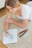 Happy young woman lying on floor sketching on paper — Stock Photo