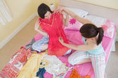 Cute girls looking at a dress at a sleepover — Stock Photo