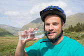 Fit man wearing bike helmet drinking water — Stock Photo