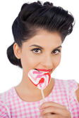 Cheerful black hair model chewing a heart shaped lollipop — Stock Photo