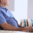 Mature man on the sofa typing on his laptop — Stock Video #31527121
