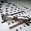 Black glasses falling onto eye test — Stock Video