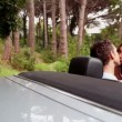 Stock Video: Beautiful young couple kissing in a convertible car