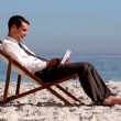 Stock Video: Smiling businessmusing tablet and relaxing on beach