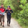Couple walking along a country trail looking at map — Stock Video