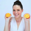 Attractive woman holding slices of orange — Stock Video #31528023