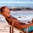 Young man sitting on the beach — Stock Video #31528303