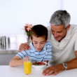 Stock Video: Father teasing son while he is having his breakfast