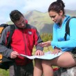 Stock Video: Couple using map and compass to find way on rock