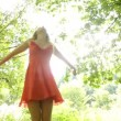 Stock Video: Beautiful teen twirling in sunlight under trees