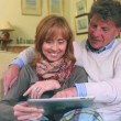 Mature couple sitting on the couch using their tablet pc — Stock Video