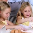 Twin sisters making pastry with their parents — Stock Video